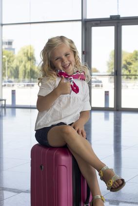空港スーツケースにすわる女の子